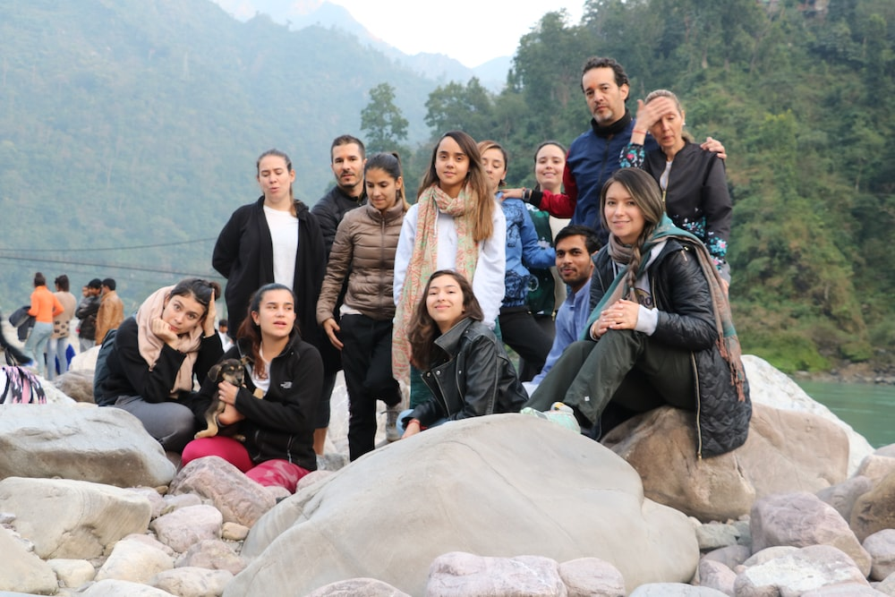 group of people sitting on rock during daytime