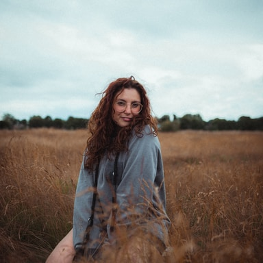 woman in blue long sleeve shirt sitting on brown grass field during daytime