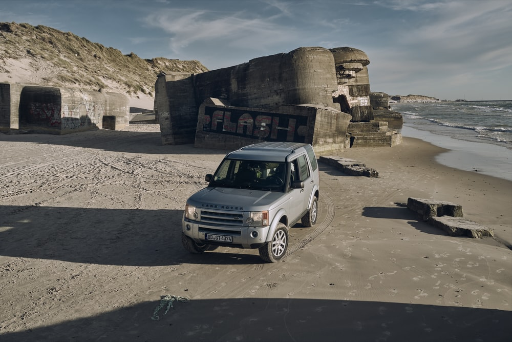 white suv parked on gray sand during daytime