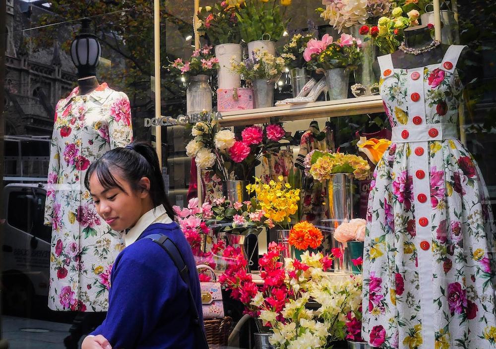 woman in blue cardigan standing beside flowers