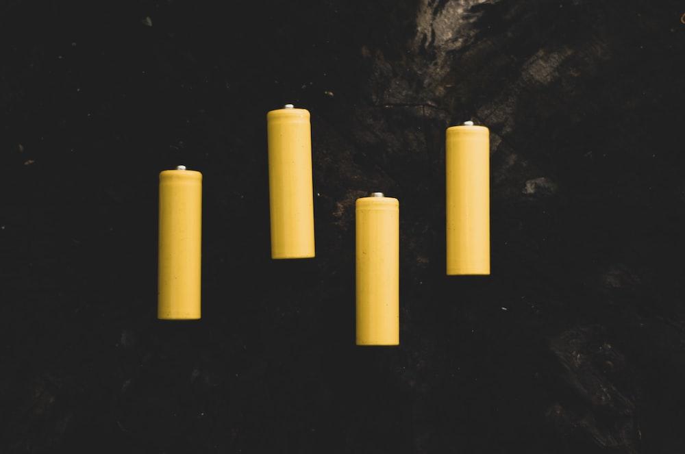 yellow pillar candles on black surface