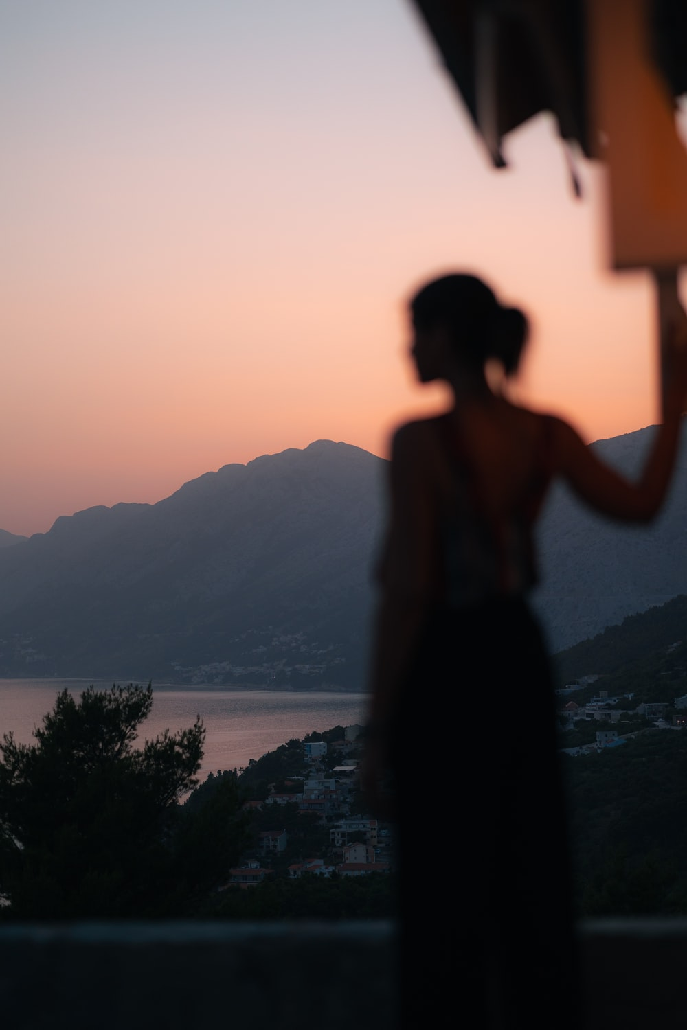 silhouette of woman standing on rock near body of water during sunset