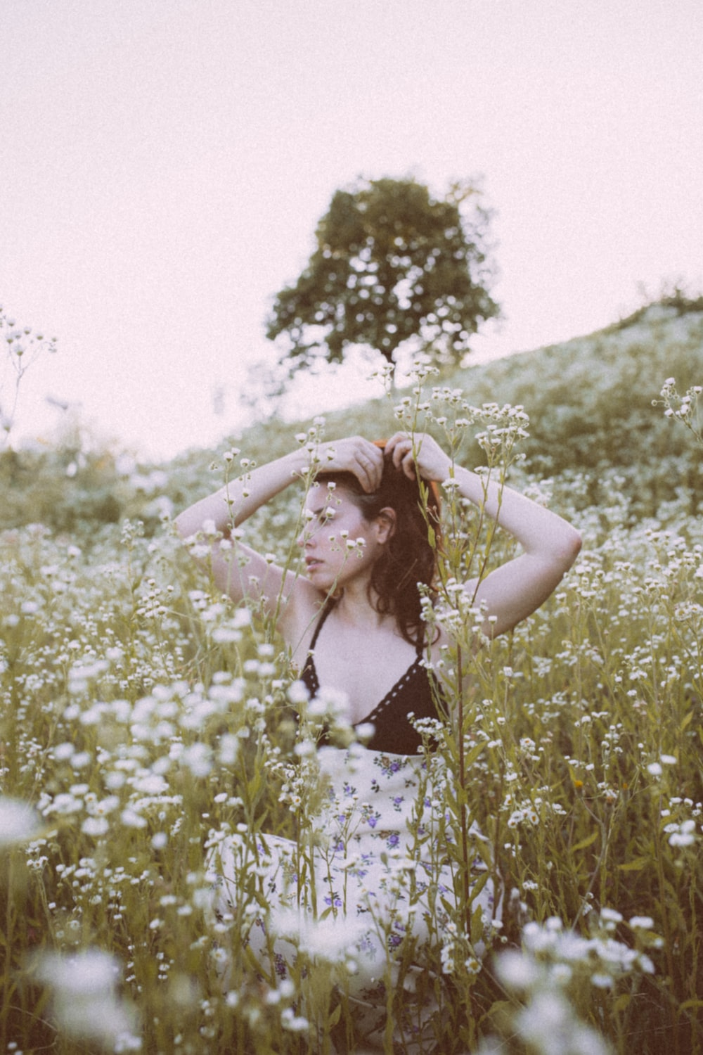woman in blue and white floral spaghetti strap top standing on green grass field during daytime