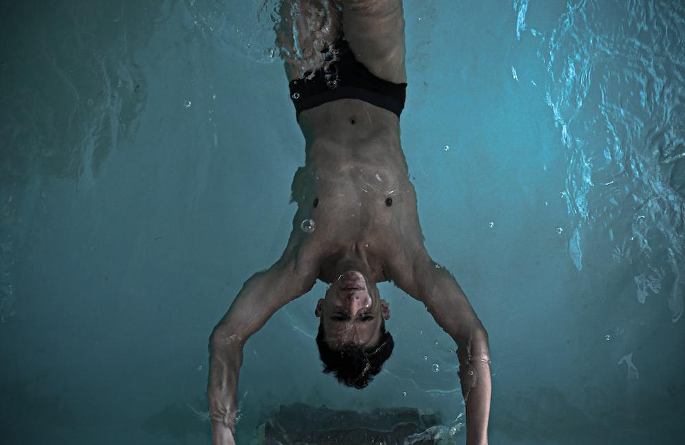 man in black shorts swimming in pool