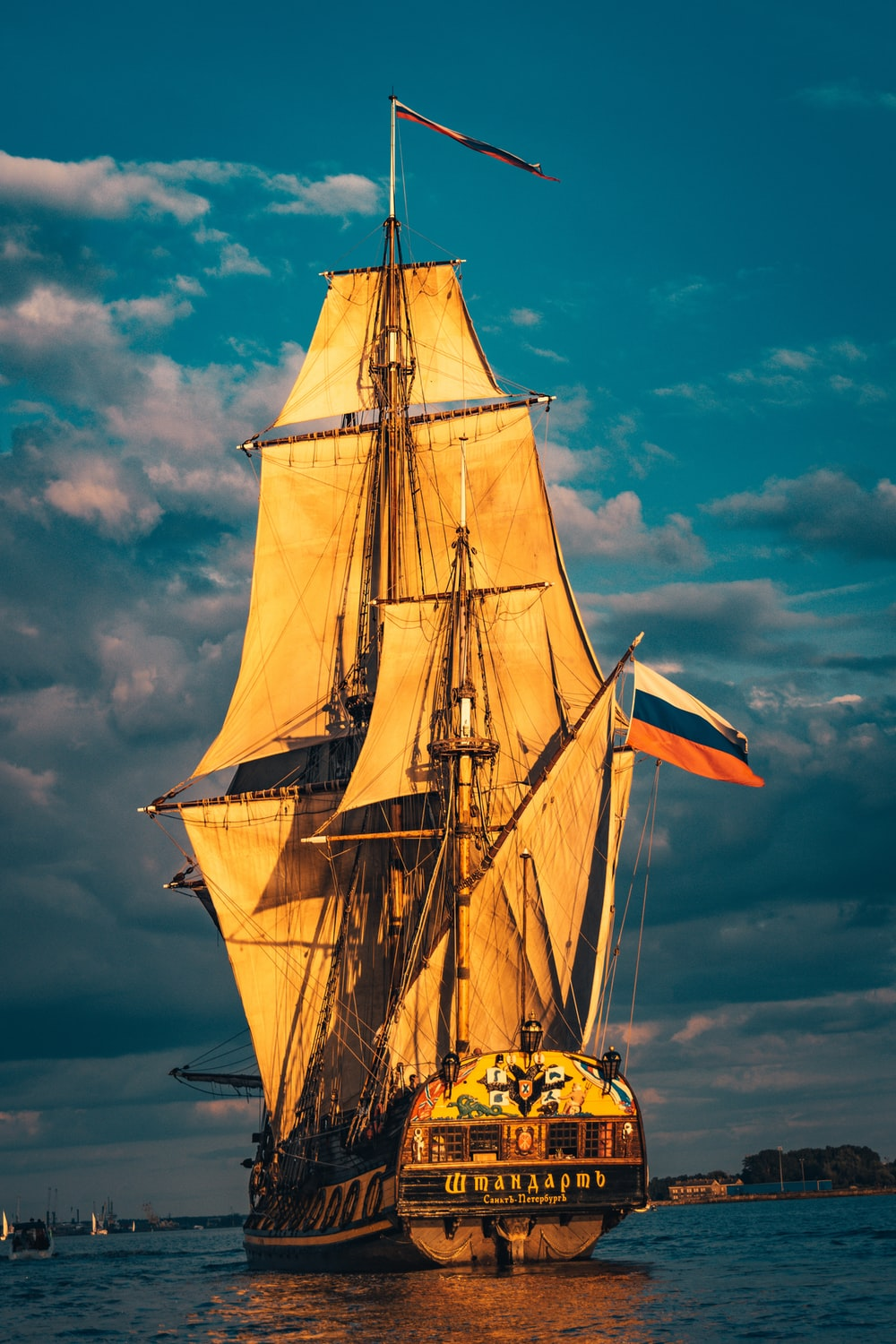 brown sail ship on sea under blue sky during daytime