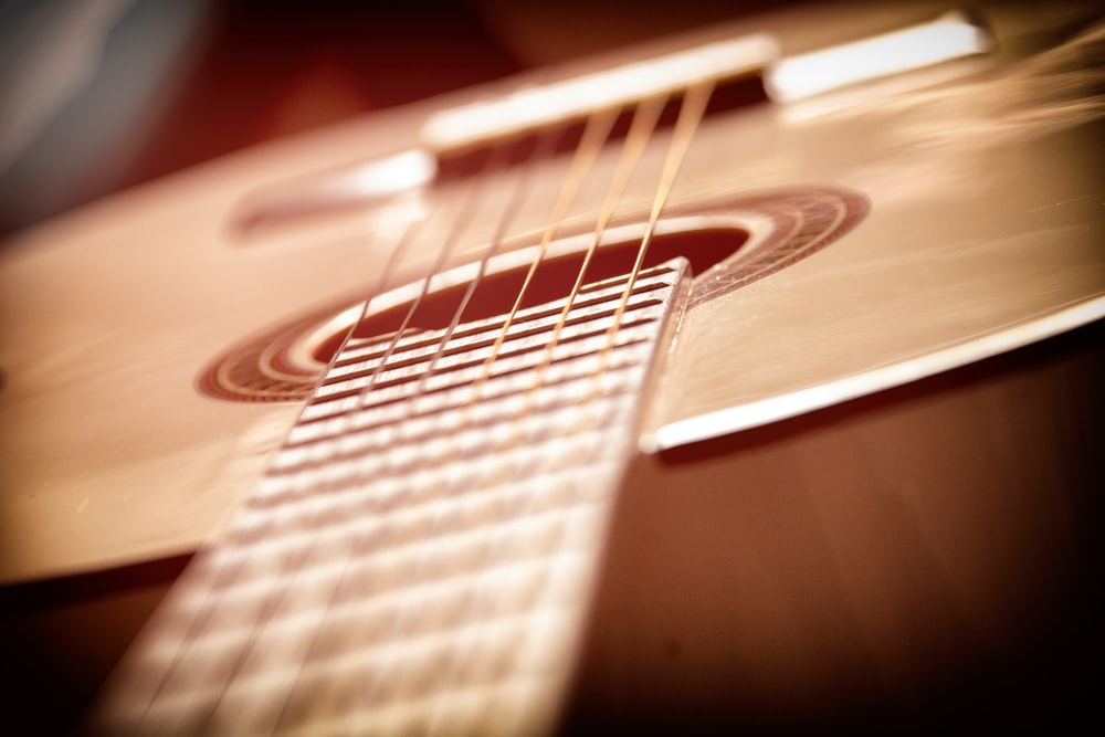 brown and white acoustic guitar