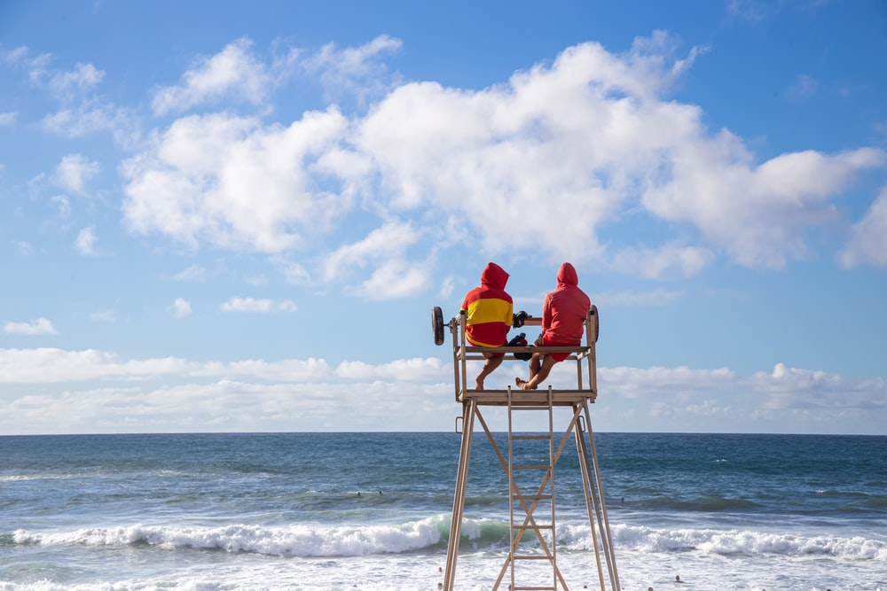 person in red hoodie sitting on brown wooden chair on beach during daytime