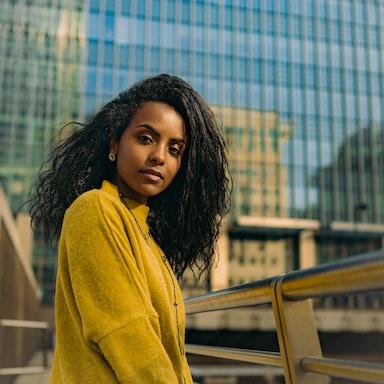 woman in yellow sweater standing beside brown metal railings