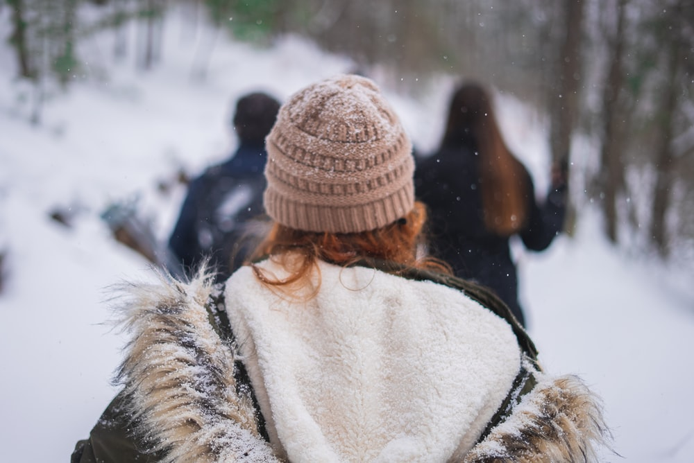 woman in white and brown fur coat wearing brown knit cap