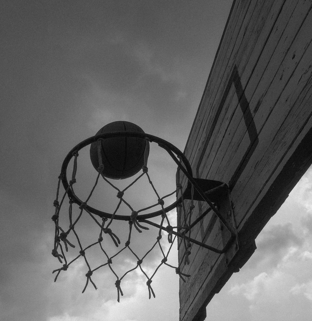 basketball hoop under cloudy sky in grayscale photography