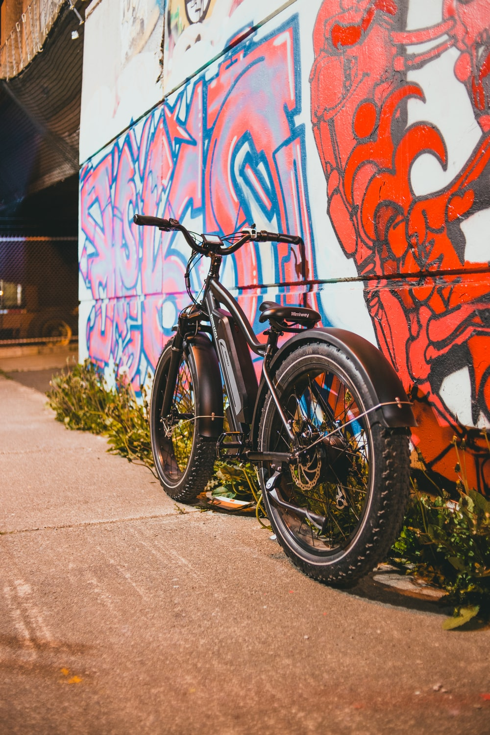 black and orange mountain bike parked beside wall with graffiti