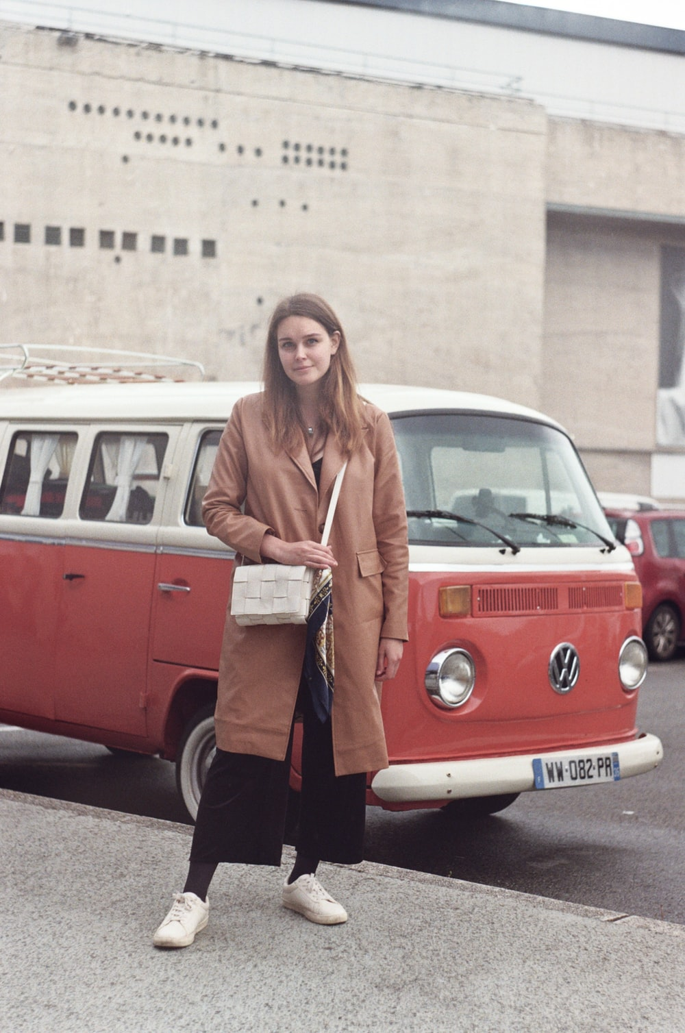 woman in brown coat standing beside red and white volkswagen t-1