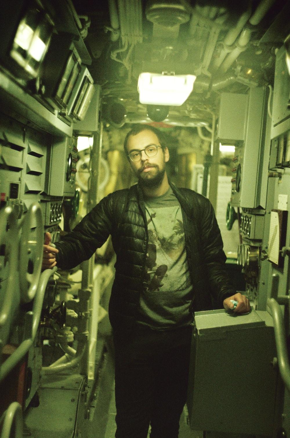 man in black leather jacket standing beside white metal rack