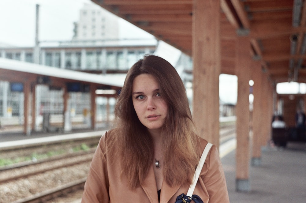 woman in brown leather jacket standing on train rail during daytime