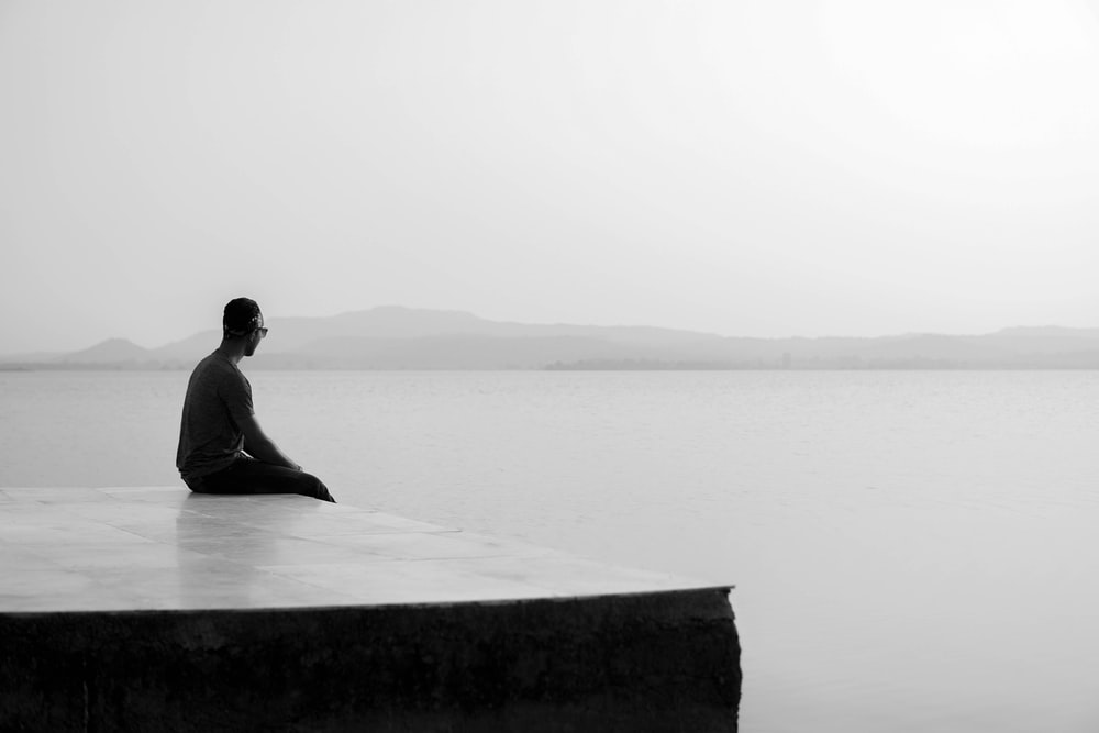 man sitting on concrete bench near body of water