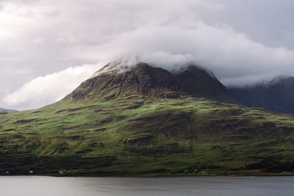 green and brown mountain under white clouds