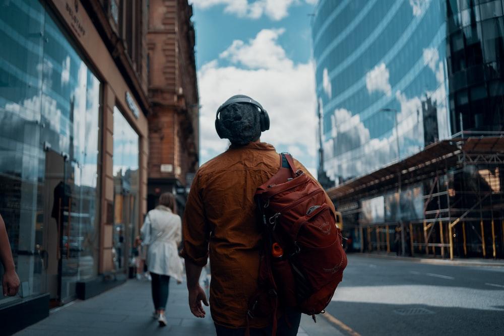 man in orange jacket walking on street during daytime