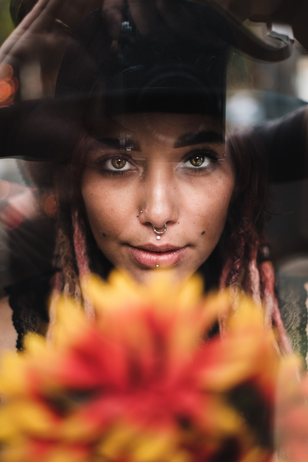 woman in black hat and yellow and red floral shirt