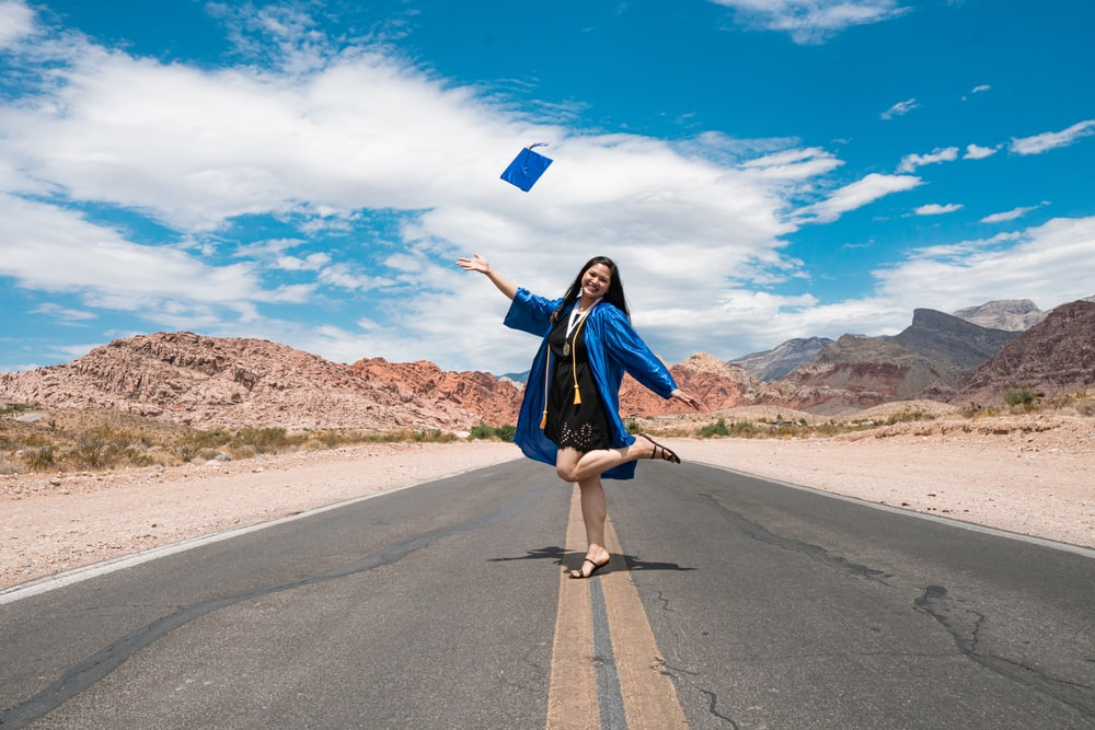 woman in blue long sleeve dress holding blue paper bag standing on gray asphalt road during
