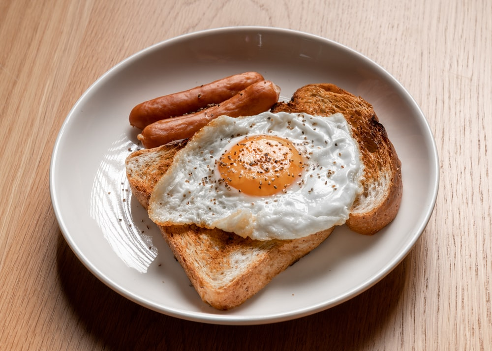 bread with sunny side up egg on white ceramic plate