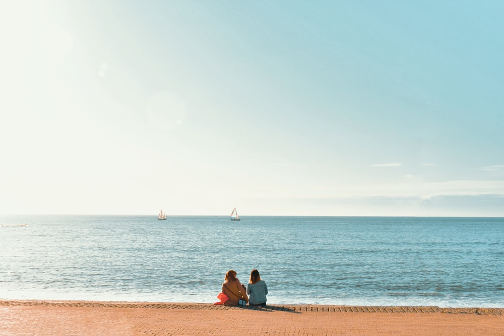man and woman sitting on brown sand near body of water during daytime
