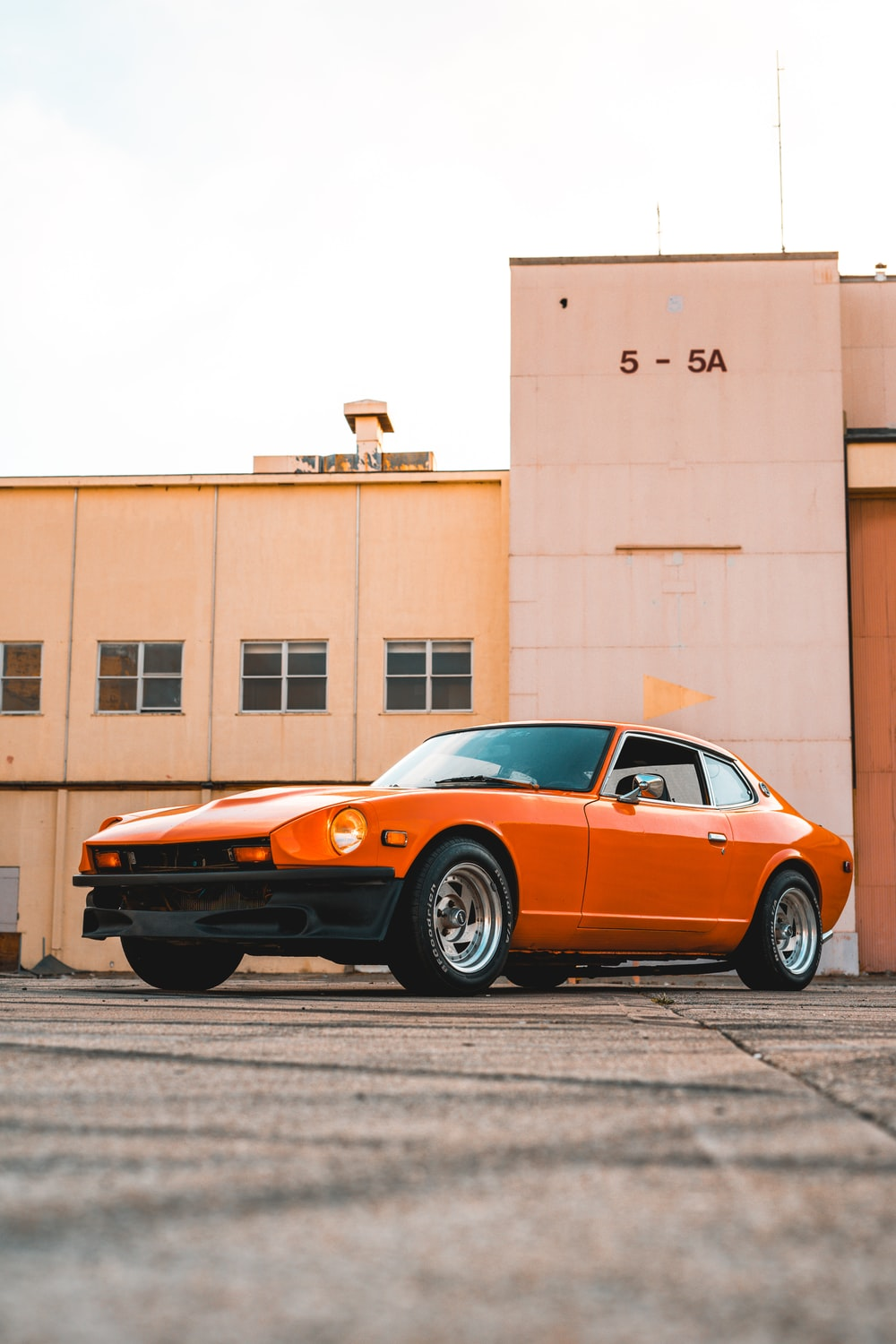 orange coupe parked beside brown building