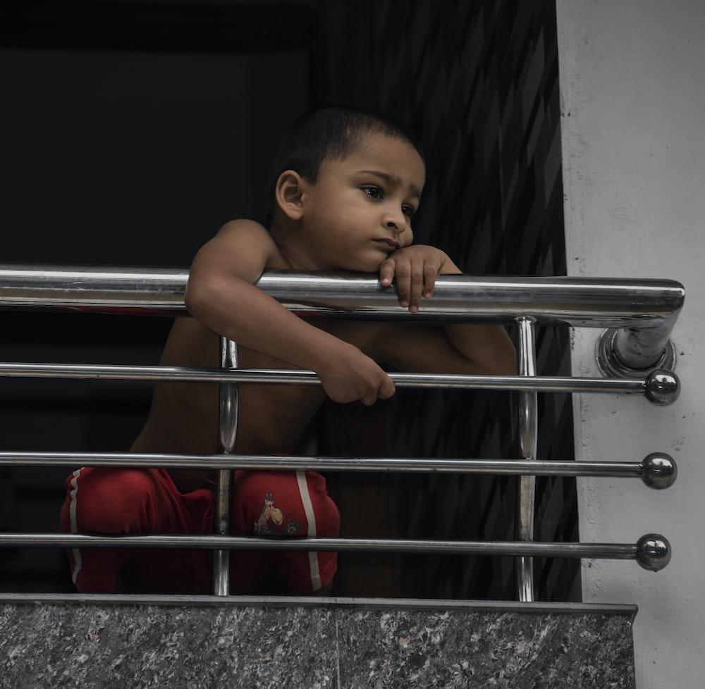 baby in red pants on stainless steel railings
