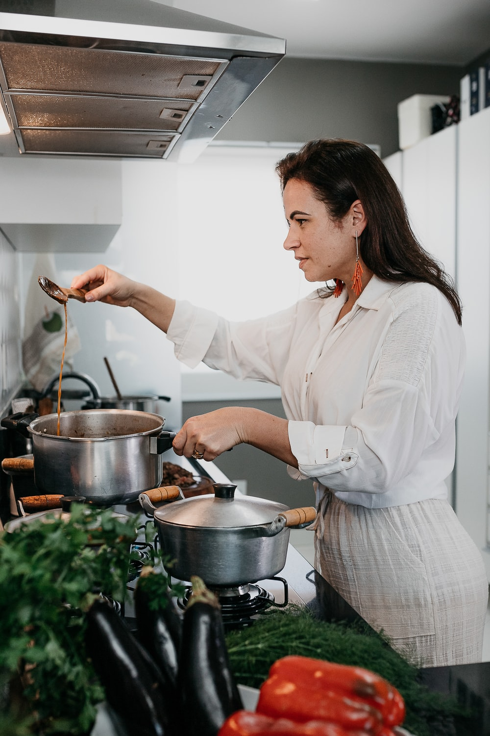 woman in white dress shirt holding stainless steel cooking pot