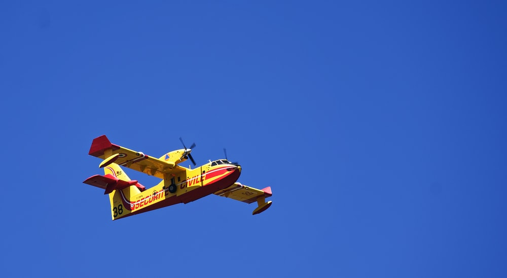 red and yellow plane flying under blue sky during daytime