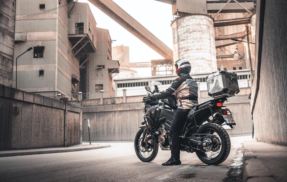 man in black motorcycle helmet riding black motorcycle during daytime