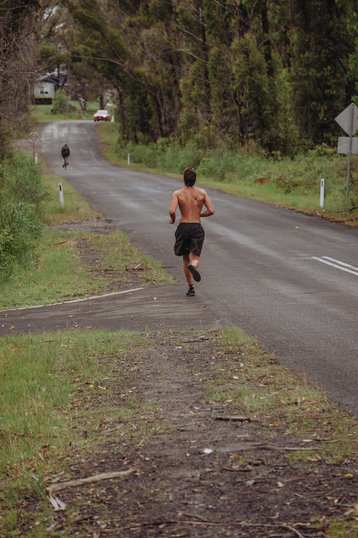 man in brown shirt running on gray asphalt road during daytime