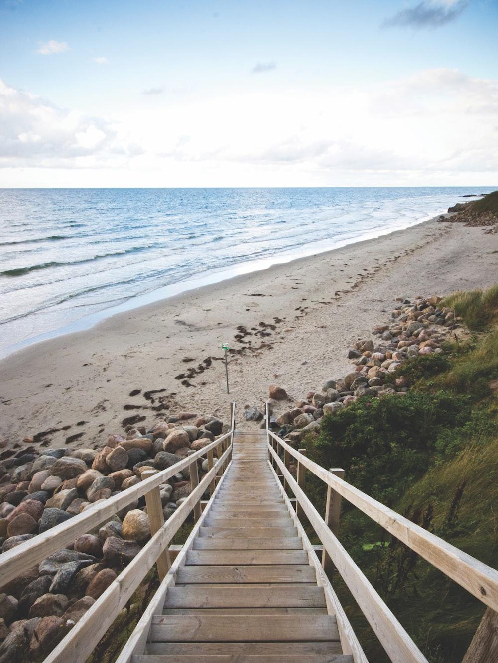 people walking on wooden bridge near beach during daytime