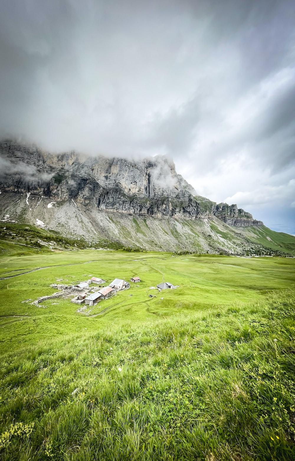 green grass field near gray mountain under white sky during daytime