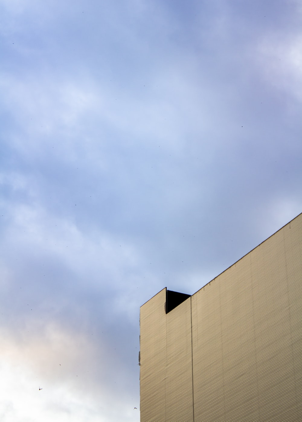 brown concrete building under white clouds during daytime