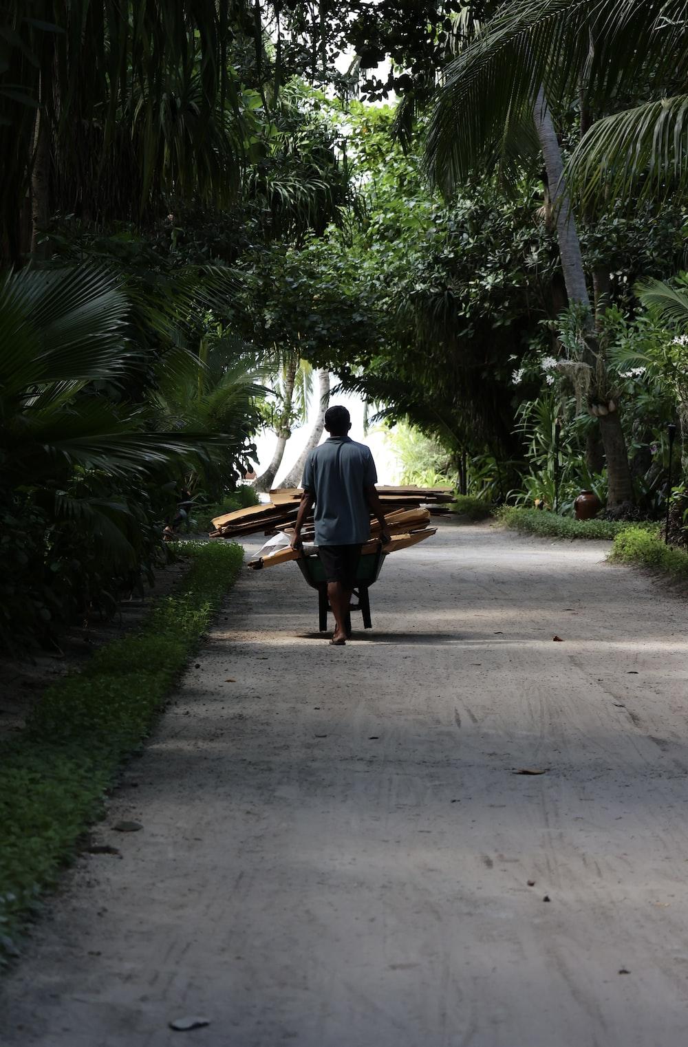 man in white shirt sitting on bench near palm trees during daytime