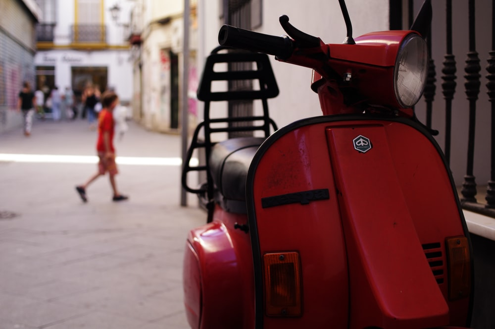 red and black motor scooter parked on the street during daytime