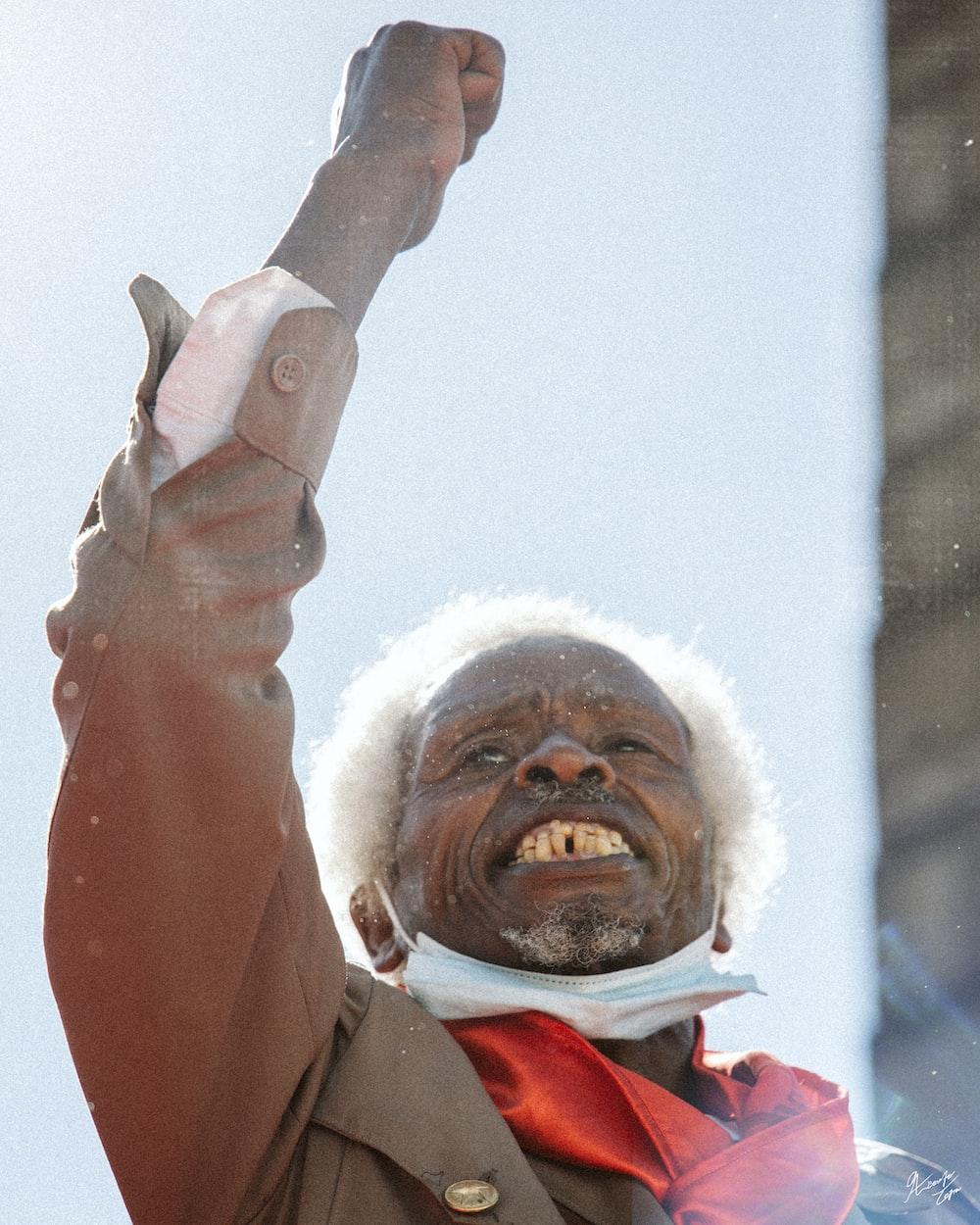 man in brown coat raising his right hand