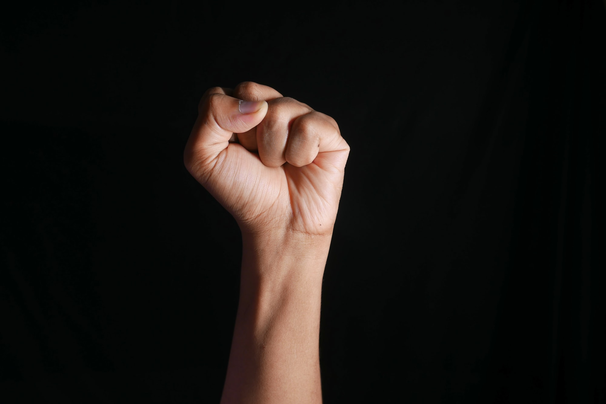 hands clenched power strength isolated on black ,