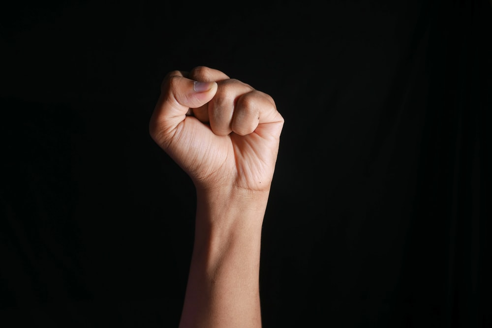 persons right hand doing fist gesture