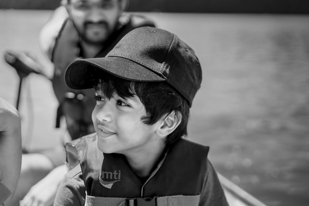grayscale photo of boy wearing hat and coat