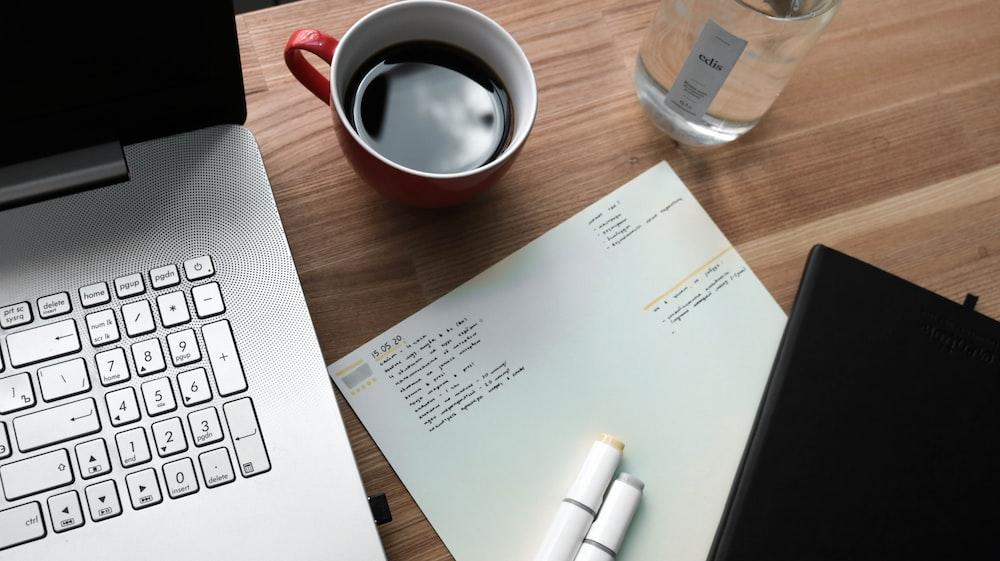 white printer paper beside white ceramic mug on brown wooden table