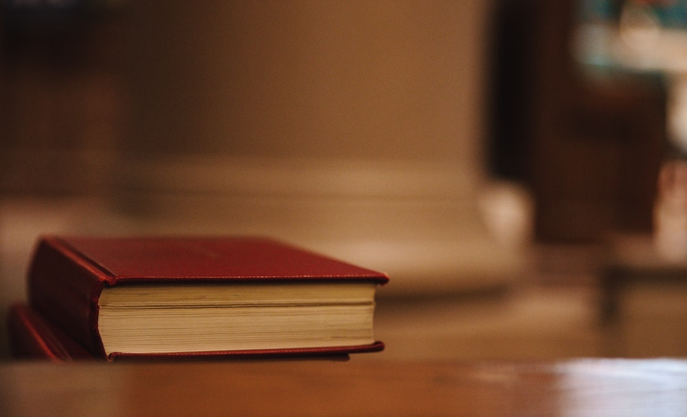 red hardbound book on brown wooden table