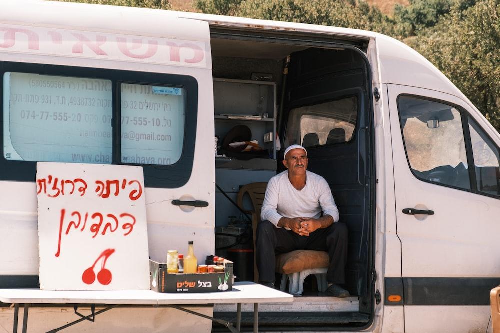 man in white dress shirt sitting on white van