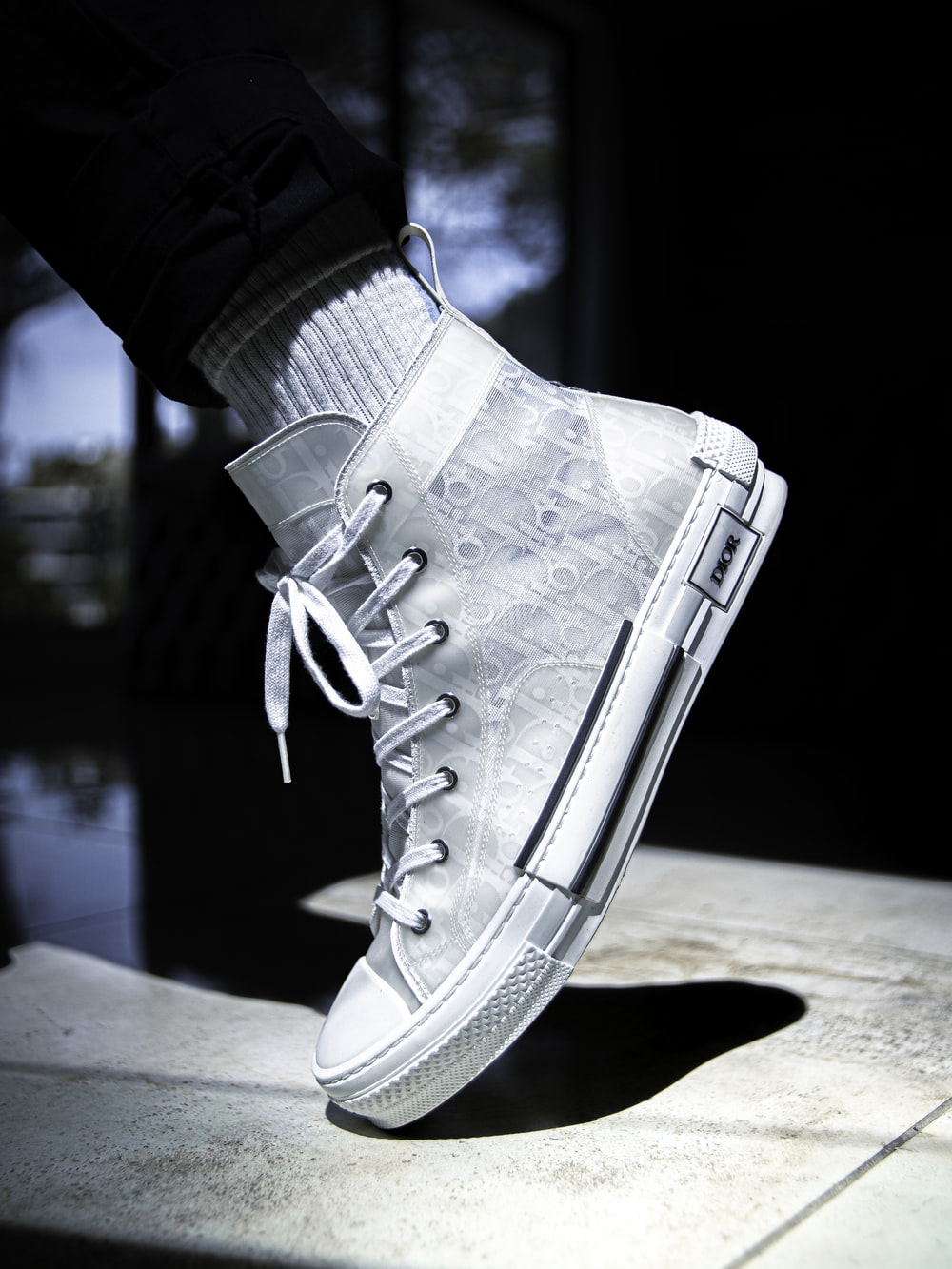 person wearing white high top sneaker