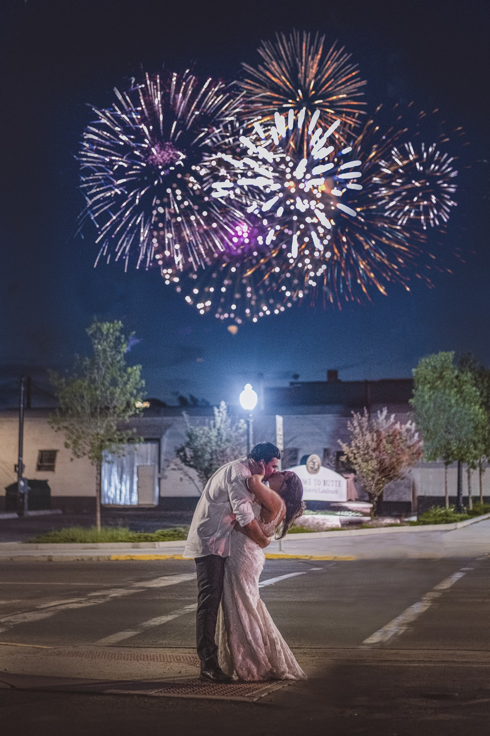 man in white dress shirt standing near pink and white fireworks during night time