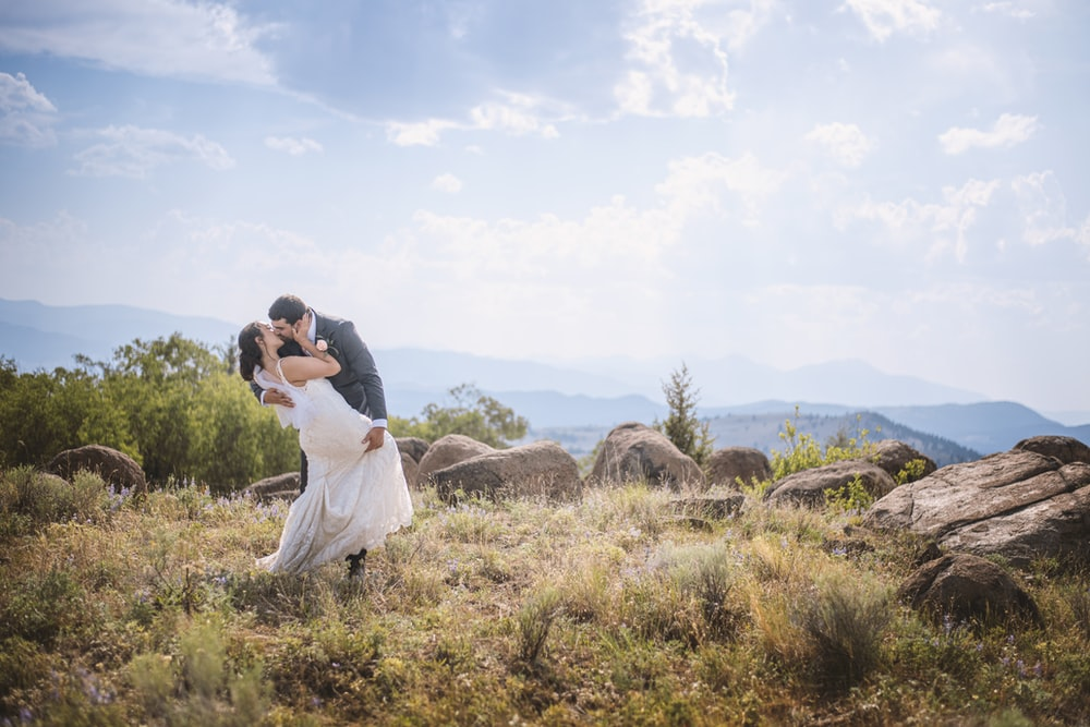 man and woman kissing on brown grass field during daytime