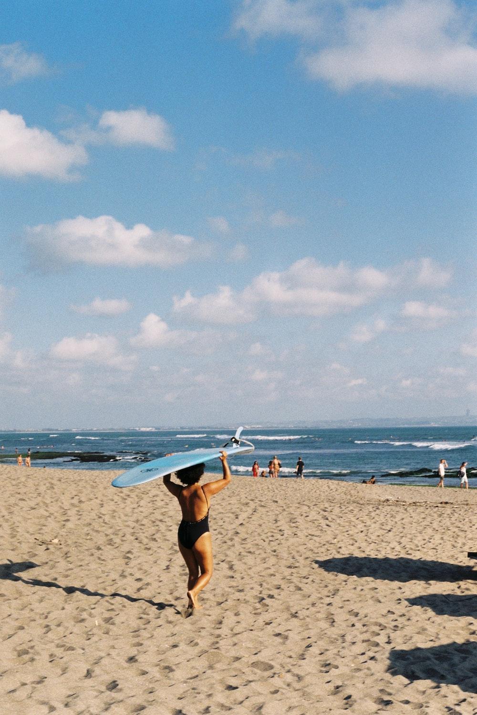 woman in white bikini holding white surfboard walking on beach during daytime