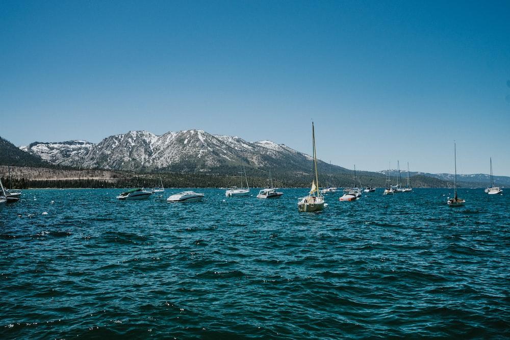 white boat on sea near mountain during daytime