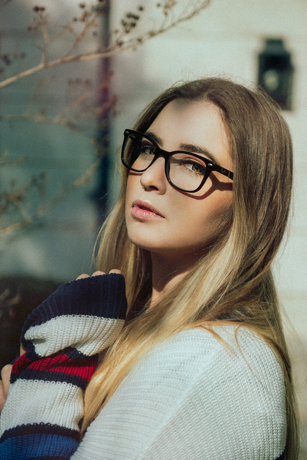 woman in white and black sweater wearing black framed eyeglasses