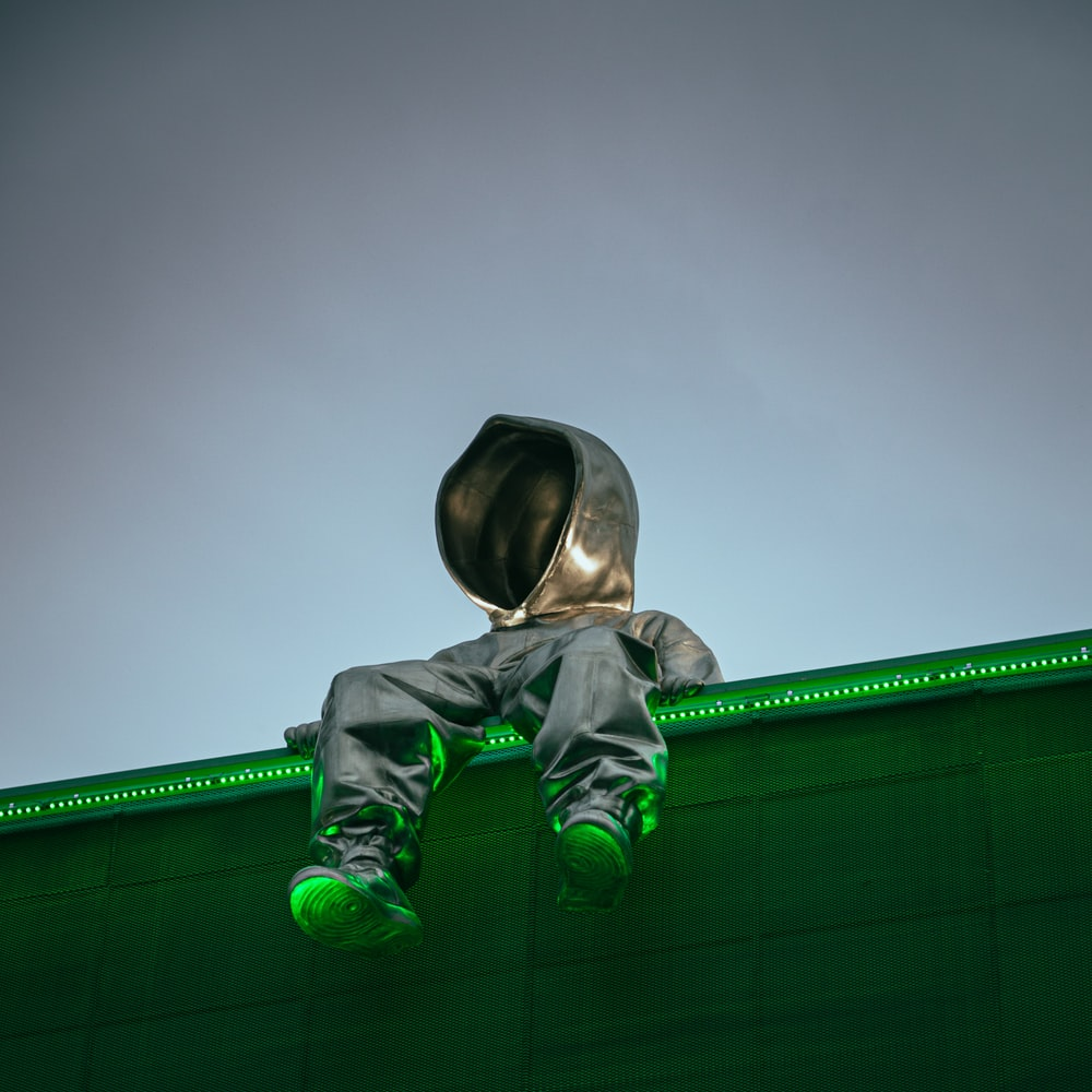 man in green hoodie and black pants sitting on green bench